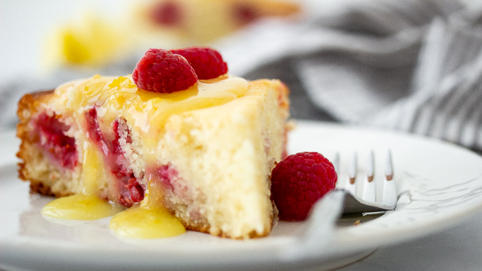 a picture of raspberry ricotta cake topped with lemon curd glaze