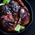 a skillet with butterflied roasted chicken with pomegranate glaze