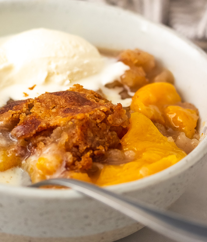 a bowl of southern peach cobbler with ice cream