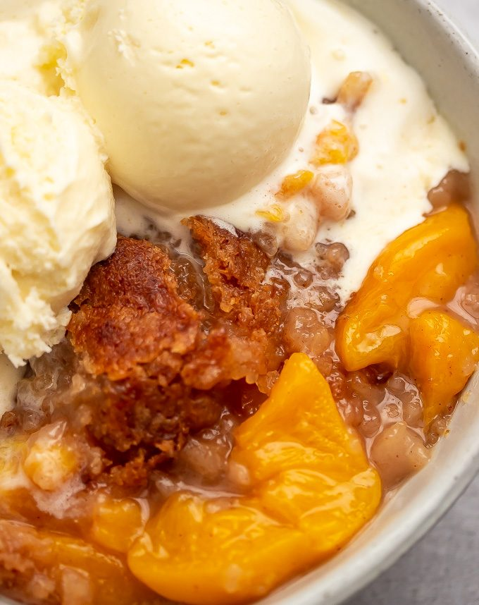 A bowl of ice cream with buttery crisp topping peach cobbler