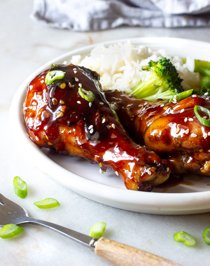 A plate of teriyaki chicken legs with rice and broccoli