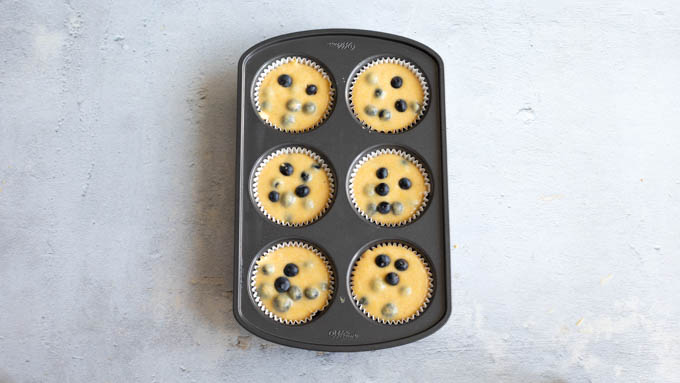 blueberry corn muffin batter in the muffin tin