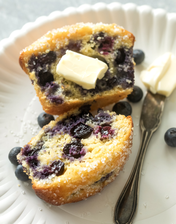 Jumbo Blueberry corn muffins ona plate with butter
