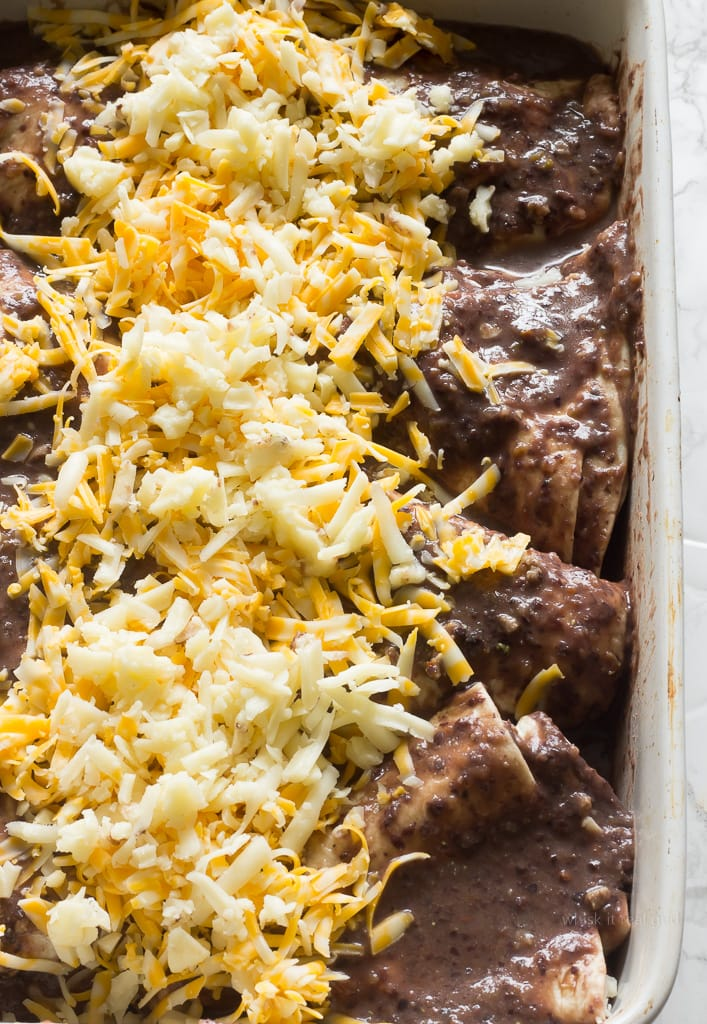 If you love Mexican food then you will love this enfrijolada recipe. Enfrijoladas are similar to enchiladas. Instead of using enchilada sauce, black bean sauce is used. They are traditionally made using corn tortillas, with chorizo, chicken or cheese slathered in a black bean or pinto bean sauce, topped with crumbled queso fresco. This enfrijolada recipe uses flour tortillas, ground beef and 3 different cheeses: monterey jack, colby and queso fresco! You can serve enfrijoladas with salsa, shredded lettuce, avocado, cilantro, radishes, sour cream. Whatever you like! It's so good!