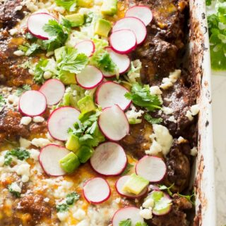 Enfrijoladas are similar to enchiladas. Instead of using enchilada sauce, black bean sauce is used. They are traditionally made using corn tortillas, with chorizo, chicken or cheese slathered in a black bean or pinto bean sauce, topped with crumbled queso fresco. This enfrijolada recipe uses flour tortillas, ground beef and 3 different cheeses: monterey jack, colby and queso fresco! You can serve enfrijoladas with salsa, shredded lettuce, avocado, cilantro, radishes, sour cream. Whatever you like! It's so good!
