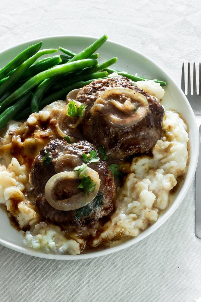 Seasoned flavorful beef patties cooked in a caramelized rich onion gravy. So delicious! This classic American meal comes together quickly & easily. Serve with mashed potatoes and string beans. An ultimate and warming comfort food!