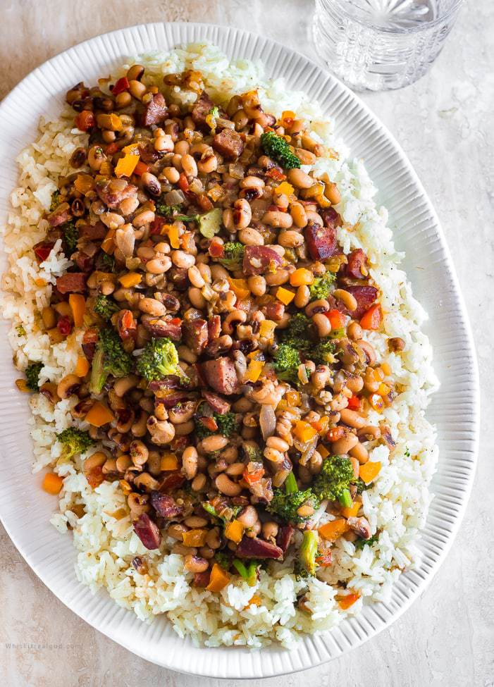 Traditional Hoppin John is thought to bring luck and prosperity. It's a staple New Year's day dinner in the south, especially in South Carolina. Classic Hoppin John is made with ham hocks or bacon and cooked in one pot. My quick version uses, smoked sausages and more vegetables like healthy broccoli, frozen black-eyed peas and for kick, a couple pinches of crushed red peppers. This is an easy hearty dish that's ready in 30 minutes or less. a picture of Black-eyed peas and rice with vegetables