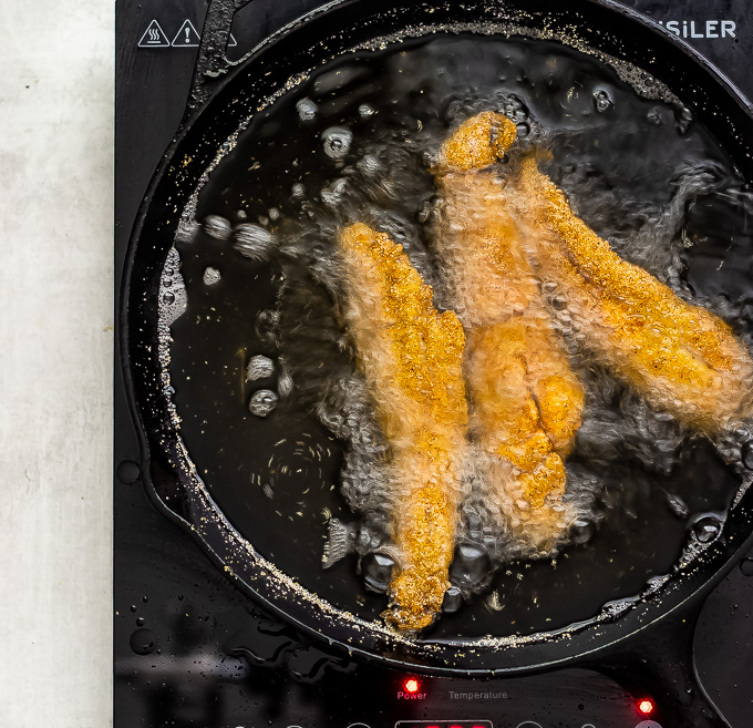 Fried whiting fish frying in skillet with hot oil.