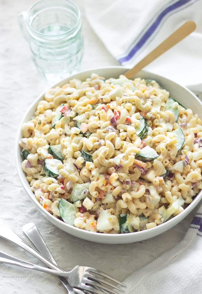 A bowl of boiled macaroni with diced cucumbers, mini peppers, onions, mayonnaise, sweet relish, mustard, salt and pepper and seasonings. Creamy macaroni salad with cucumbers and eggs is a twist on the traditional classic American macaroni salad. You will not believe how delicious this pasta salad is