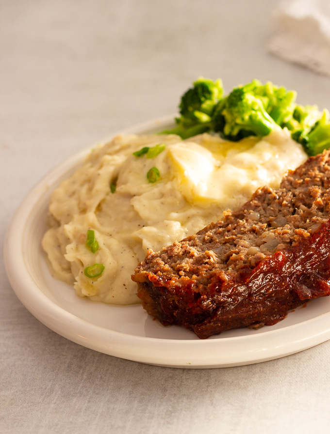 A plate of meatloaf with mashed potatoes and broccoli
