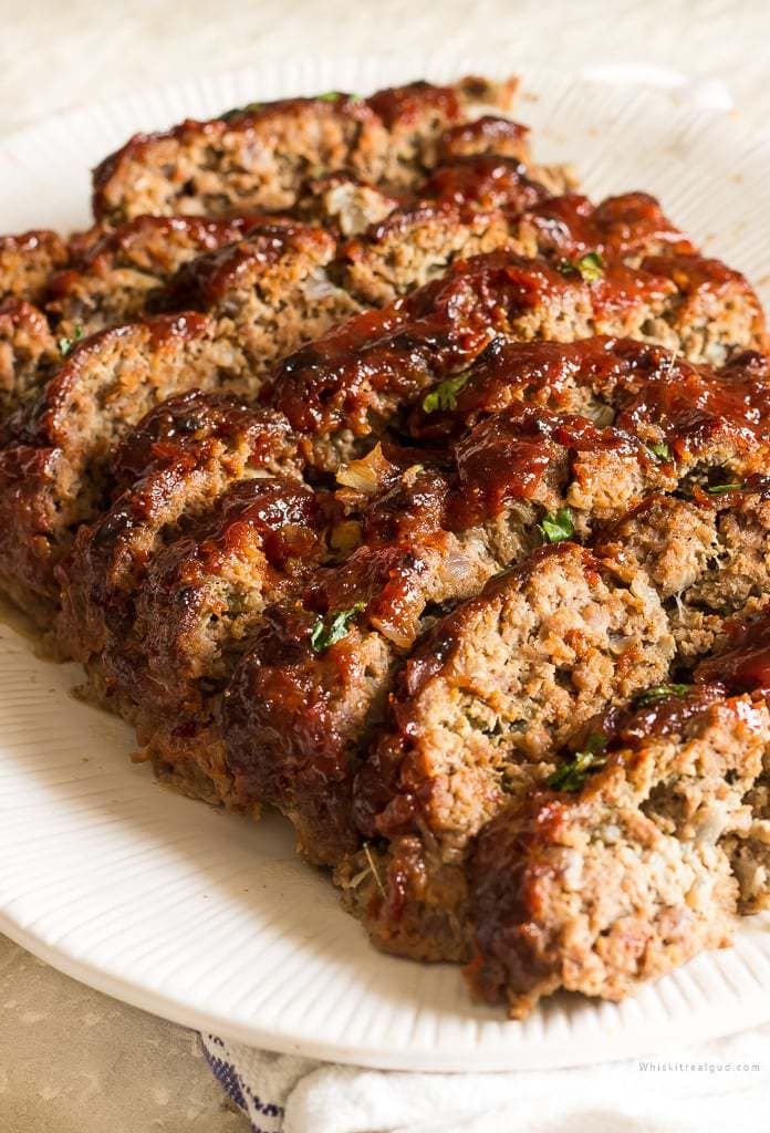 Slices of meatloaf with a brown sugar ketchup glaze on a serving plate.