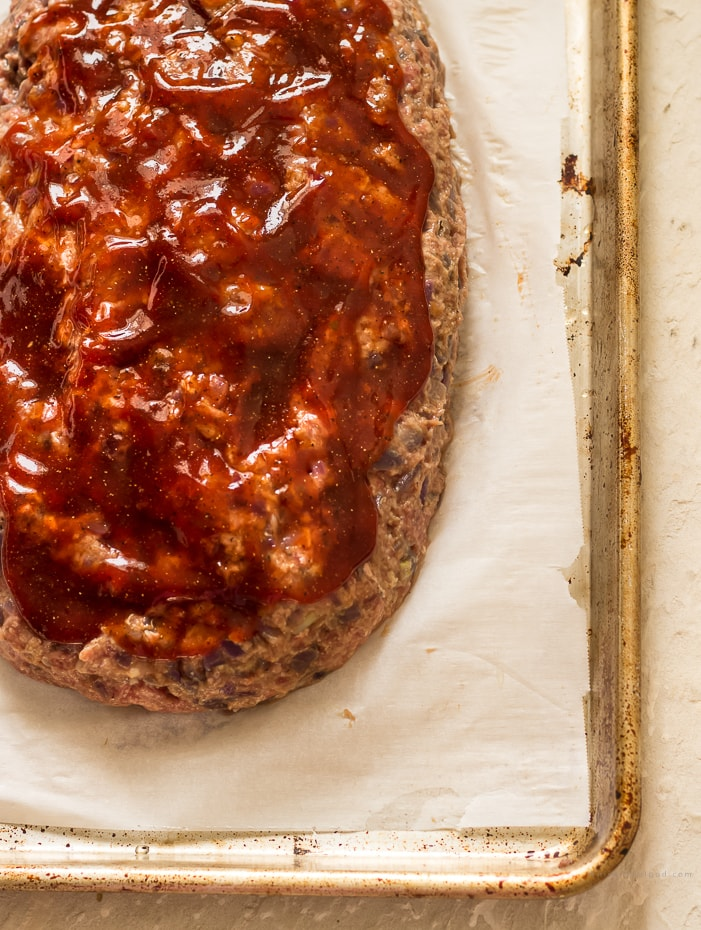 A raw meatloaf with brown sugar ketchup glaze on a parchment lined cookie sheet