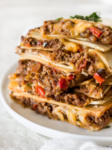 Sheet pan quesadillas that are stacked on top of one another with cheese, peppers and taco seasoning