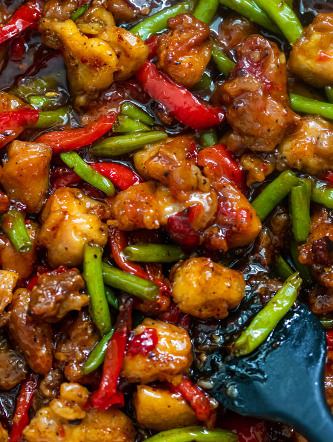 A photo of chicken stir fry with green beans in a skillet