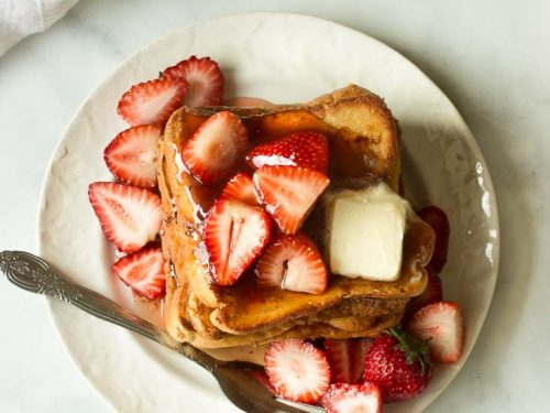 a plate of french toast topped with strawberries