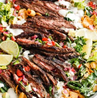 A bowl of salad with taco seasoned steak and cilantro lime dressing topped with fritos