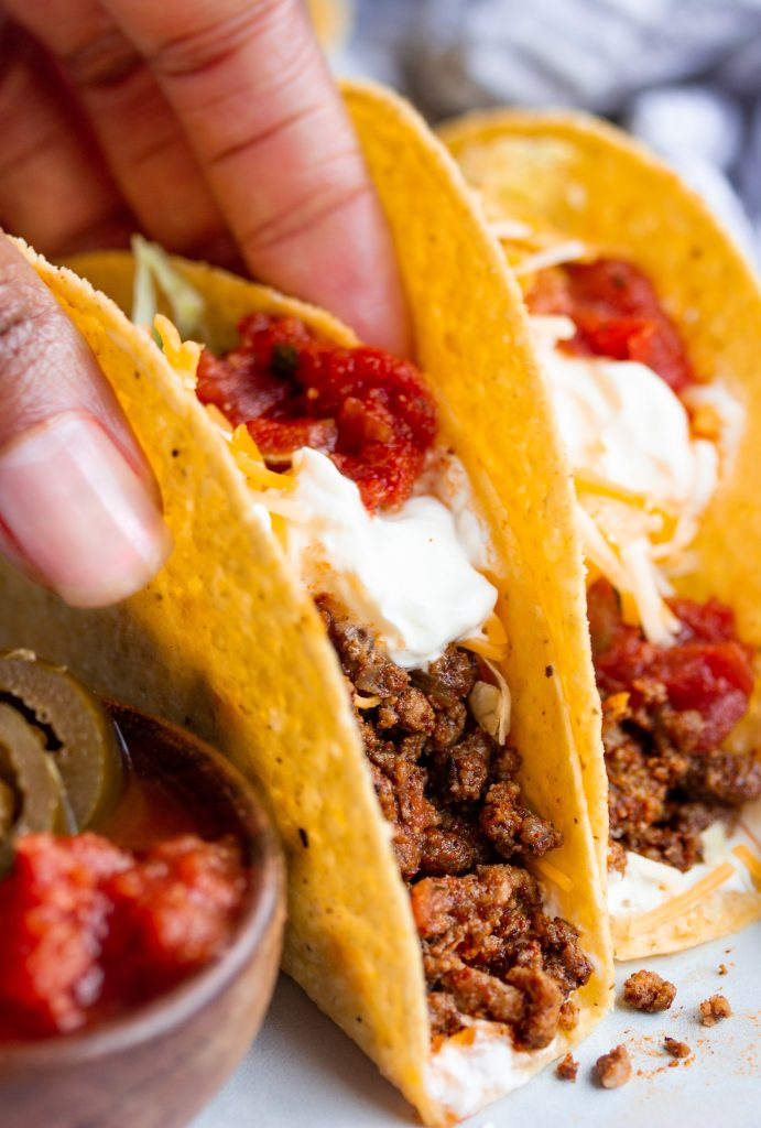 Taco seasoned ground beef tacos topped with salsa and sour cream
