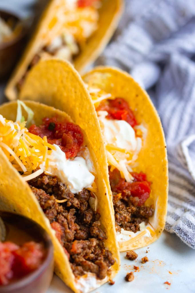 Taco seasoned ground beef tacos topped with salsa and sour cream in a corn tortilla shell