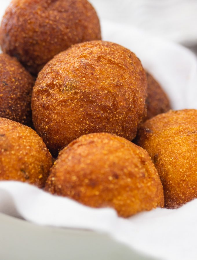 a bowl of golden brown round hush puppies
