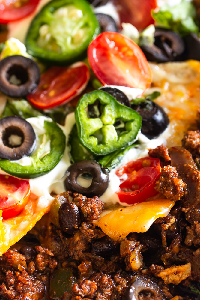 taco bake with taco seasoned ground beef, melted cheese, tortilla chips topping, more melted cheese, garnished with lettuce, sour cream, black olives, jalapenos and tomatoes.