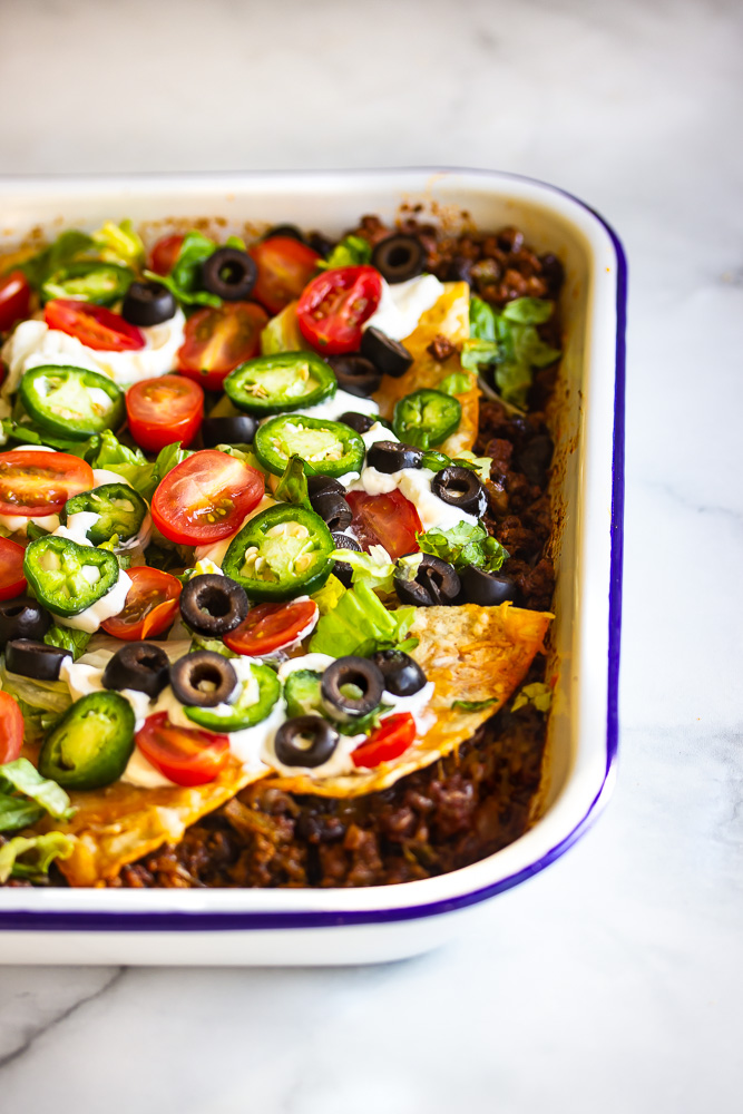 taco casserole with taco seasoned ground beef, melted cheese, tortilla chips topping, more melted cheese, garnished with lettuce, sour cream, black olives, jalapenos and tomatoes.