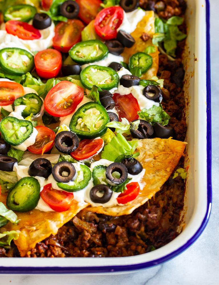 A pan with taco seasoned ground beef topped with shredded cheeses and tortilla chips and jalapenos, beans and tomatoes