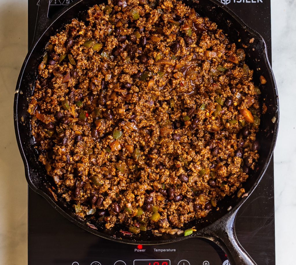a skillet of taco seasoned ground beef with black beans, onions and green peppers