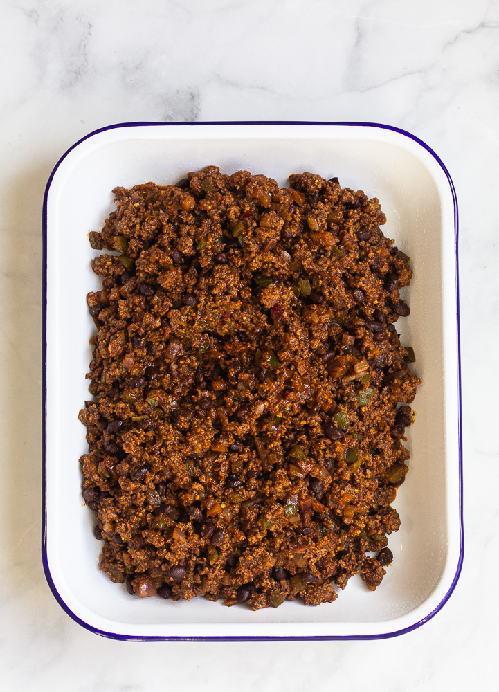A pan of taco seasoned ground beef with black beans, onions and green peppers