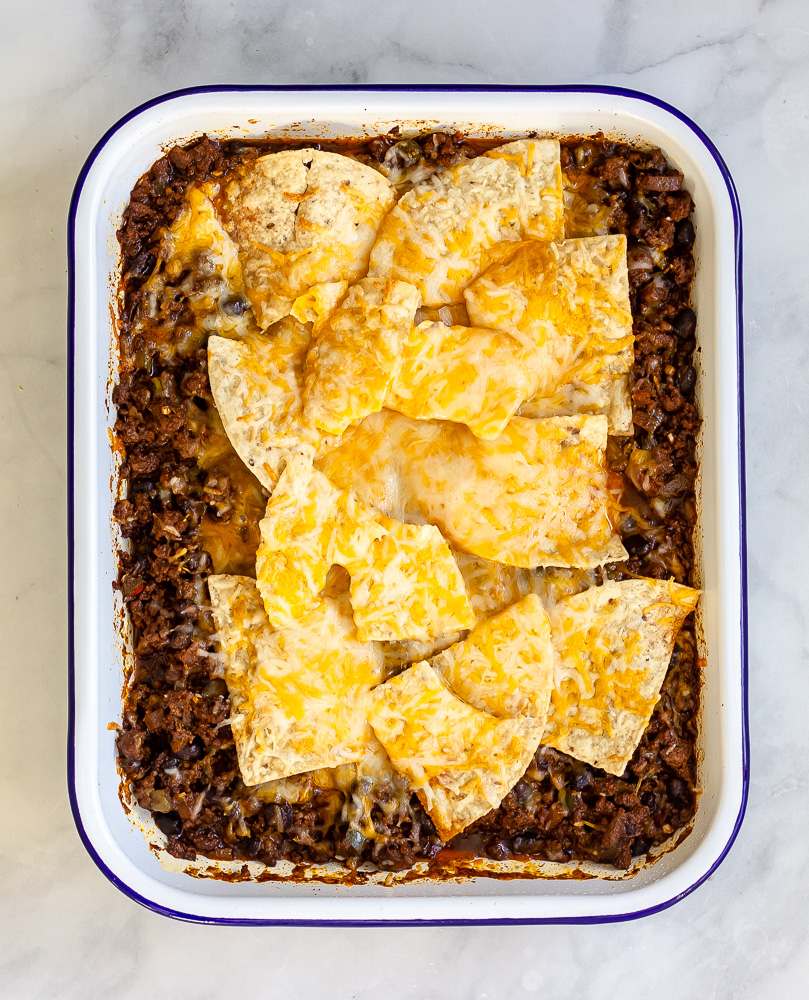 A pan of taco seasoned ground beef with black beans, onions and green peppers topped with melty Mexican cheese topped with tortilla chips with melted cheese on top.