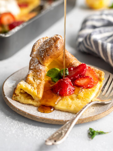 A picture of a slice of a dutch baby pancake on a plate topped with strawberries