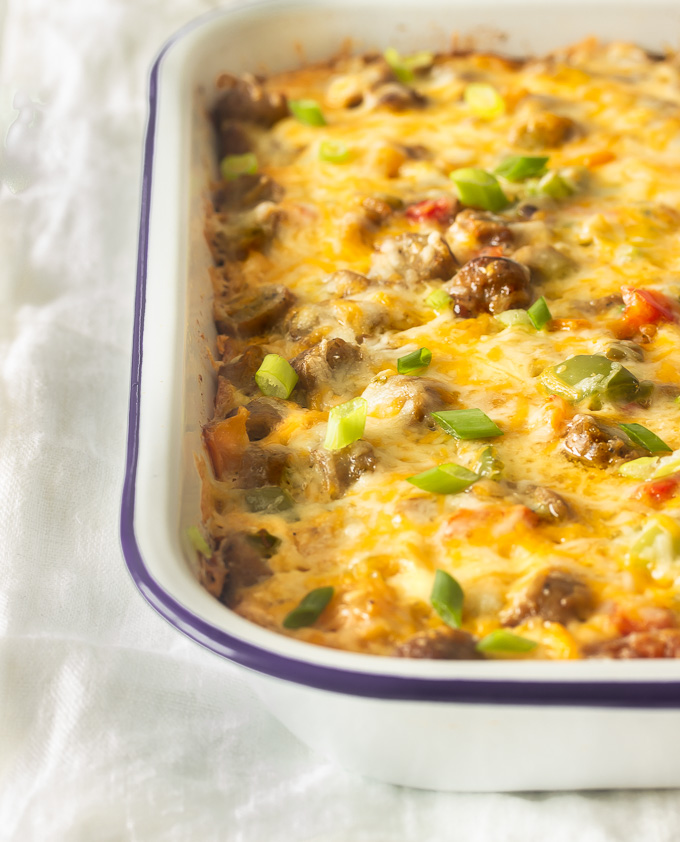 A tater tot breakfast casserole in a pan with crispy tater tots, eggs, melted cheese, sausages, peppers and onions.