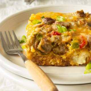 A tater tot breakfast casserole with crispy tater tots, eggs, melted cheese, sausages, peppers and onions.