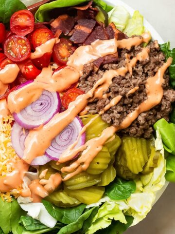 A cheeseburger in a bowl salad in a bowl with seasoned ground beef, grape tomatoes, red onions, pickles, turkey bacon and shredded cheese with special sauce