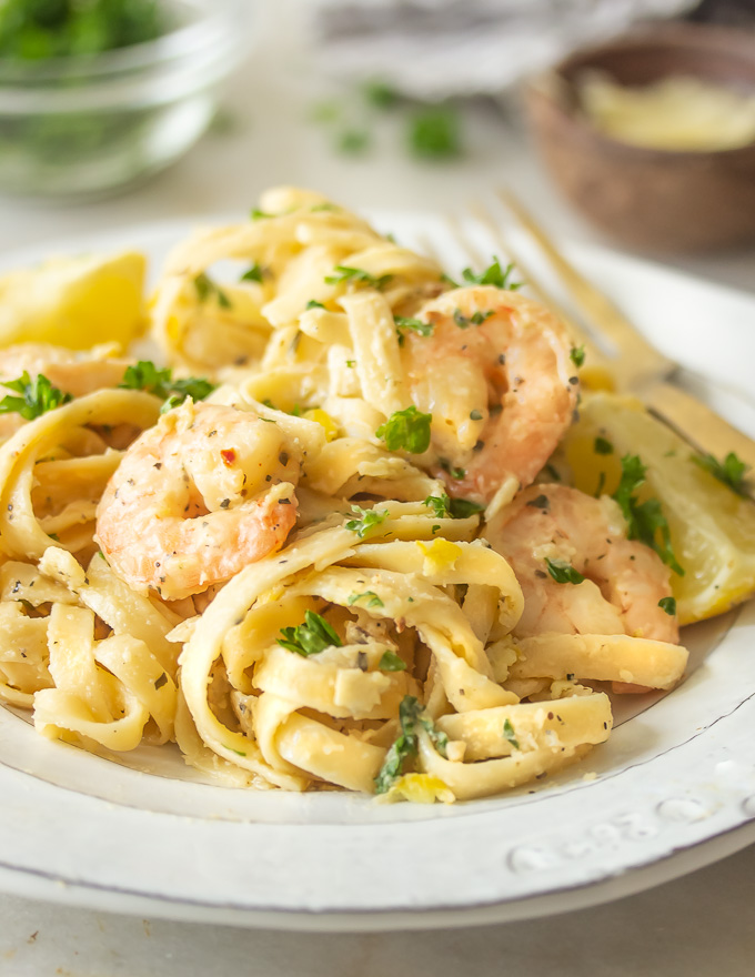 A plate of lemon garlic parmesan shrimp pasta with zested lemon and parmesan cheese