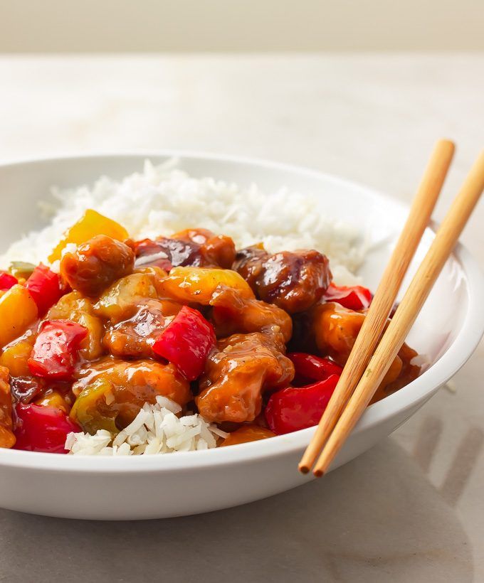 A bowl of sweet and sour chicken over rice