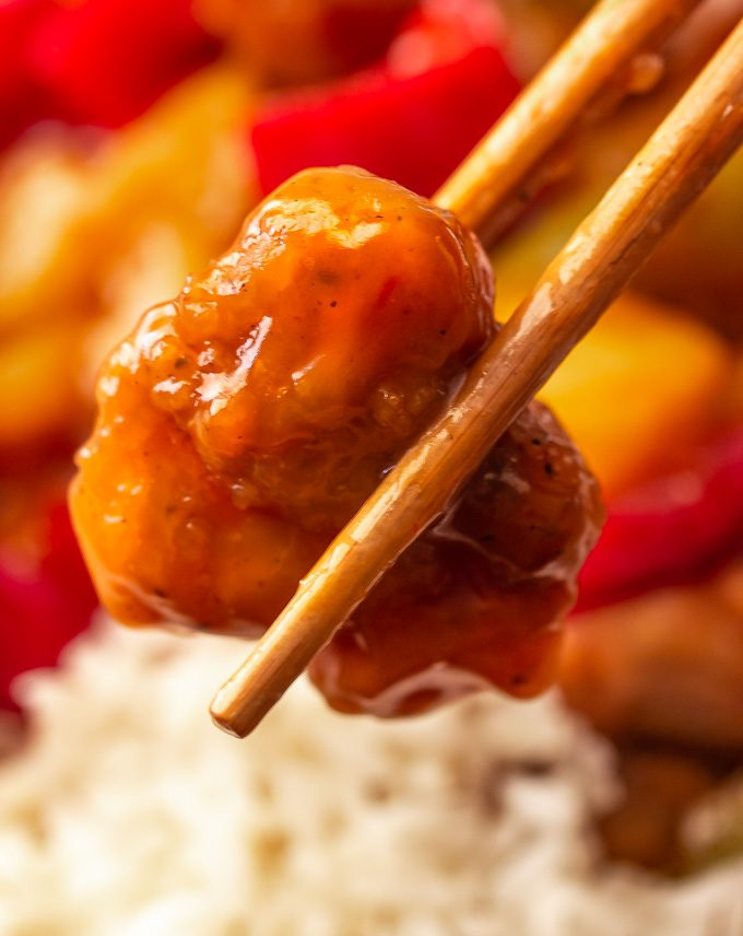 A picture of chopsticks holding a pice of sweet and sour chicken