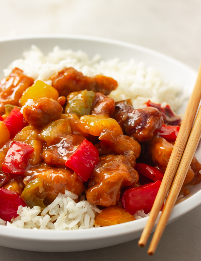 A plate of sweet and sour chicken with bell peppers, onions, pineapples tossed in a sweet and savory sauce over rice.