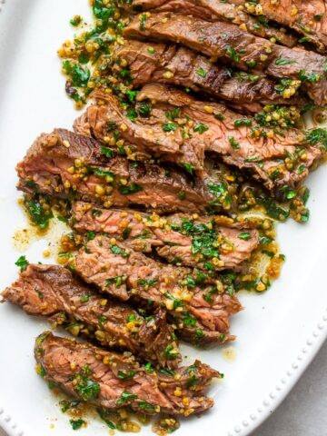 A plate of juicy tender Brazilian Steak with garlic butter drizzled on top