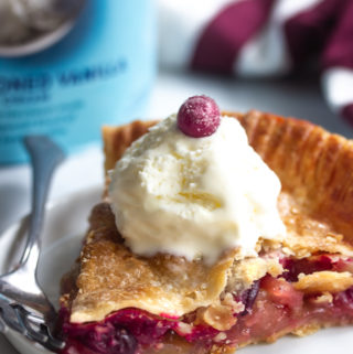 A slice of cranberry apple pie on a plate