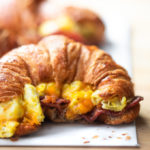 A photo of a bacon egg and cheese croissant