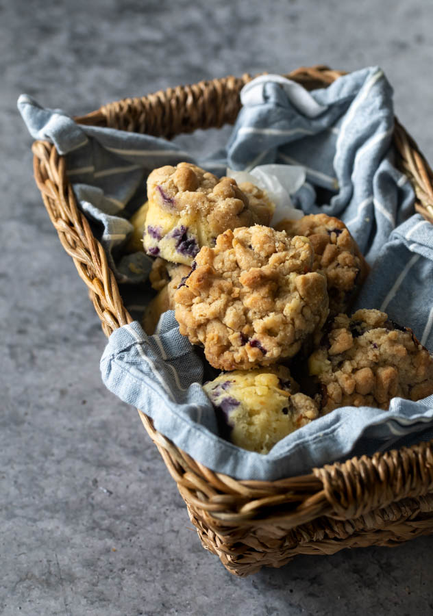 blueberry muffins with crumb top in a basket