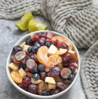 Greek yogurt creamy fruit salad with apples, blueberris, grapes, mandarins and strawberries in a bowl