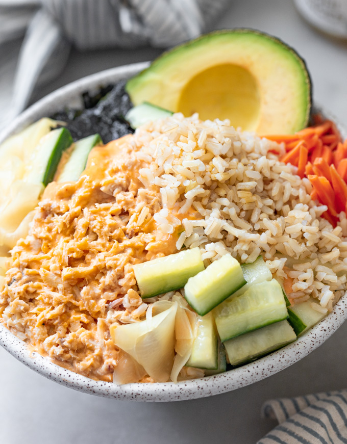 A tuna fish bowl with pickled cucmbers, carrots brown rice topped with spicy mayonnaise