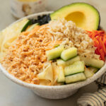 A tuna bowl with pickled cucmbers, carrots brown rice topped with spicy mayonnaise