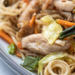 A plate of chicken chow mein with cabbage, green onions, carrots and bean sprouts