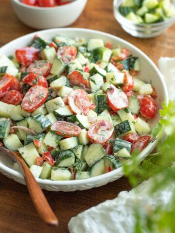 Tomato cucumber salad in a bowl with creamy dill dressing