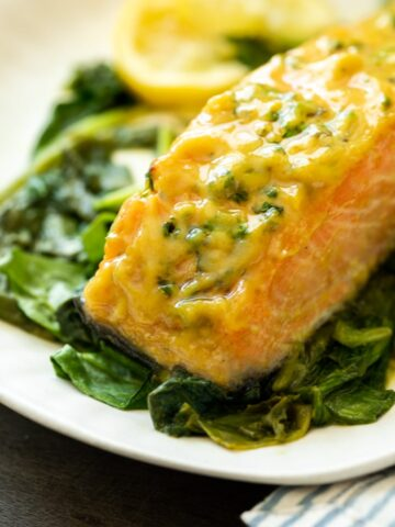 A picture of honey mustard salmon cooked in the oven with roasted spinach and honey mustard sauce