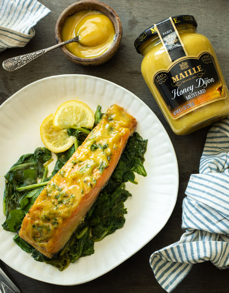 A picture of a plate of honey mustard salmon that's been roasted with spinach