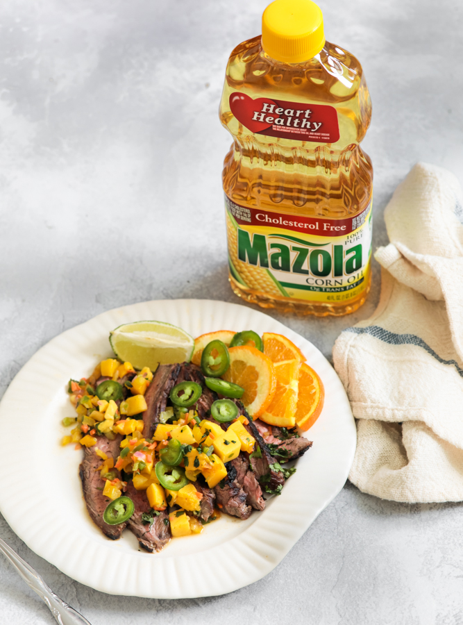 Jerk steak with mango salsa on a white plate with a bottle of mazola heart healthy corn oil behind it