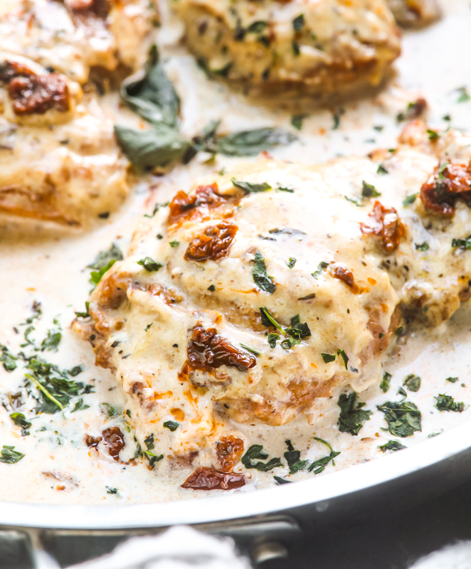 A picture of creamy chicken thighs in a basil cream sauce in a skillet